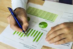 Businessman analyzing sustainable development chart. Businessman analyzing sustainable development opportunities charts at workspace. Hand holding a pen and Royalty Free Stock Photo