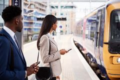 Free Businessman And Businesswoman Commuting To Work On Railway Platform Waiting For Train Stock Images - 157266894