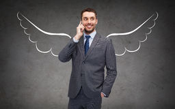 Businessman with angel wings calling on cellphone Stock Photography