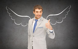Businessman with angel wings showing thumbs up Stock Photo