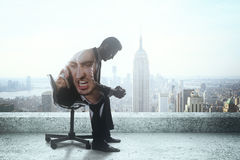 Businessman with anger issues. Sad businessman with anger issues sitting on rooftop with New York city view. Double exposure stock image