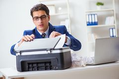 The businessman angry at copying machine jamming papers. Businessman angry at copying machine jamming papers Royalty Free Stock Photography