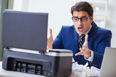 The businessman angry at copying machine jamming papers. Businessman angry at copying machine jamming papers Stock Photos