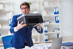 The businessman angry at copying machine jamming papers. Businessman angry at copying machine jamming papers Royalty Free Stock Image