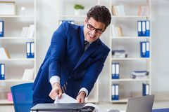 The businessman angry at copying machine jamming papers. Businessman angry at copying machine jamming papers Royalty Free Stock Photos