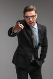 Businessman angry and shouting over isolated grey background. Stock Photos