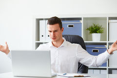 Businessman is angry while working on laptop. Young businessman is angry while working on laptop Stock Photography