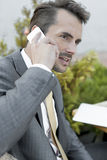Businessman answering cell phone outdoors Royalty Free Stock Photography