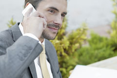 Businessman answering cell phone outdoors Stock Photos