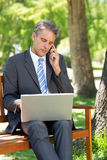 Businessman answering cellphone while using laptop Royalty Free Stock Photo