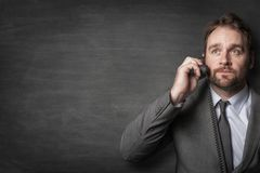 Businessman answering on cord phone stock image