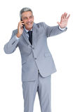 Businessman answering phone and waving Stock Photo
