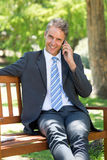 Businessman answering smart phone on park bench Royalty Free Stock Images
