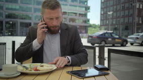 Businessman answers phone call and checks data in tablet, steadicam. stock video