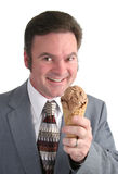 Businessman Anticipating Ice Cream. A businessman smiling as he gets ready to eat a chocolate ice cream cone royalty free stock photo
