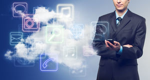 Businessman and applications icons. Businessman with touch screen phone and the cloud with applications icons on blue background royalty free stock photos