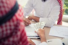 Businessman Arabian signing contract and exchange money together royalty free stock photography