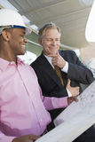 Businessman And Architect Looking At Blueprint Stock Images