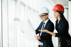 Businessman architects look at paper plan business woman architect in office to discuss business projects near panoramic window. royalty free stock photography