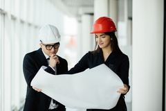Businessman architects look at paper plan business woman architect in office to discuss business projects near panoramic window. royalty free stock photos