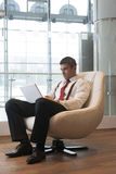 Businessman in arm chair working on laptop Stock Photos