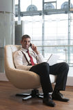 Businessman in arm chair working on laptop on the phone Royalty Free Stock Photo