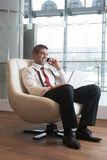 Businessman in arm chair working on laptop on the phone Royalty Free Stock Image