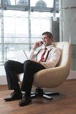 Businessman in arm chair working on laptop on the phone Royalty Free Stock Photos