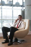 Businessman in arm chair working on laptop on the phone Stock Photo