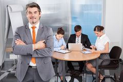 Businessman with arm crossed standing in front of his colleagues Stock Photos