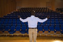 Businessman with arm stretched out standing in a auditorium. Rear view of old African-American businessman with arm stretched out standing in a auditorium stock photography