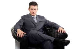 Businessman in a armchair. Young caucasian businessman in a suite, sitting in armchair Royalty Free Stock Photos