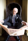 Businessman in armchair with newspaper Royalty Free Stock Photos