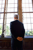 Businessman with arms behind back, looking out window, rear view Stock Image