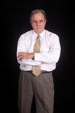 Businessman with arms crossed. Standing in is shirtsleeves, this businessman has his arms crossed and a very serious expression Royalty Free Stock Photos