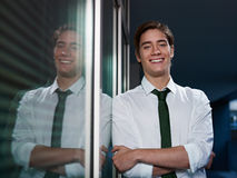 Businessman with arms crossed smiling at camera. Young business man leaning on office window with arms crossed and looking at camera smiling. Horizontal shape Stock Photo