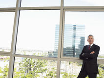 Businessman With Arms Crossed Standing By Office Window Royalty Free Stock Photography