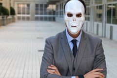 Businessman with arms crossed wearing a horrible mask royalty free stock images
