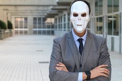 Businessman with arms crossed wearing a horrible mask stock photo