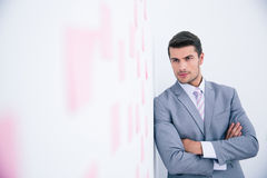 Businessman with arms folded leaning on the wall Royalty Free Stock Image
