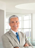 Businessman Arms Folded Office. Portrait of a middle aged businessman wearing a light tan suit with his arms folded in a modern office setting. Vertical format Stock Image