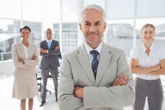 Businessman with arms folded standing in front of colleagues Stock Photos