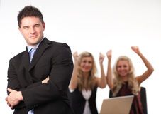 Businessman Arms Folded Team. Businessman Arms Folded with his cheering Team in the background Royalty Free Stock Images