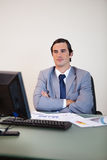 Businessman with arms folded waiting for his computer Royalty Free Stock Images
