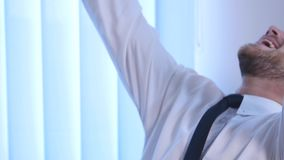 Businessman with arms raised celebrating success in office.  stock video