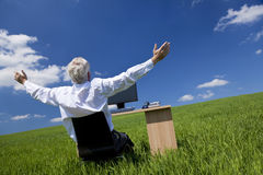 Businessman Arms Raised At Desk In Green Field. Business concept shot showing an older male executive arms raised using a computer in a green field with a blue Royalty Free Stock Photo