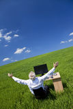 Businessman Arms Raised At Desk In Green Field. Business concept shot showing an older male executive arms raised using a computer in a green field with a blue Stock Photography