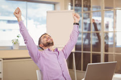 Businessman with arms raised looking up. Happy businessman with arms raised looking up in office Royalty Free Stock Images