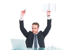 Businessman with arms up holding pencil and notebook Royalty Free Stock Image