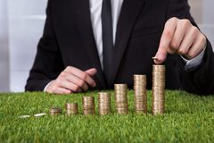Businessman arranging coins Stock Photo